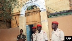 This photo taken on June 1, 2013 shows soldiers standing guard at the entrance of the main prison in Niamey.