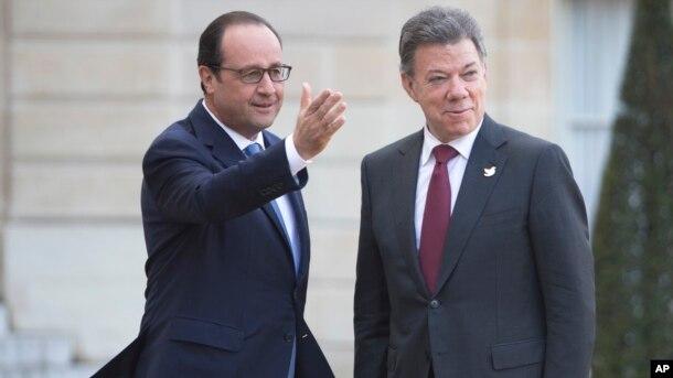 El presidente colombiano, Juan Manuel Santos y el presidente francés, Francois Hollande, firman acuerdos al final de su reunión en el Palacio del Eliseo en París, el lunes 26 de enero de 2015.