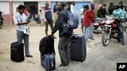 Para mahasiswa membawa barang-barang mereka saat meninggalkan kampus Universitas Kiriki di Bujumbura, Burundi, 30 April 2015. (AP Photo/Jerome Delay)