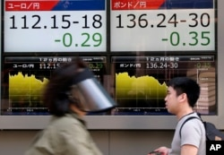 People walk by an electronic board displays exchange rate of euro, left, and British pound at the securities firm in Tokyo, June 27, 2016.