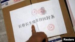 中国长春疾病控制中心的工作人员在召回的长春长生公司生产的狂犬病疫苗箱子上贴封条。(2018年7