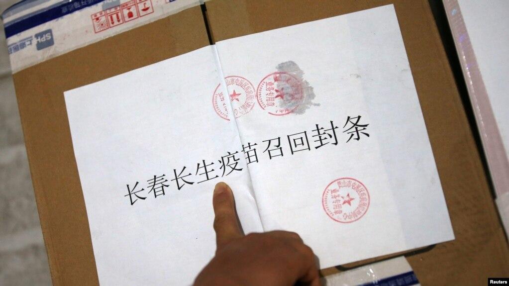 中國長春疾病控制中心的工作人員在召回的長春長生公司生產的狂犬病疫苗箱子上貼封條。 (2018年7