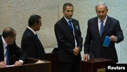 Israel's Prime Minister Benjamin Netanyahu (R) casts his ballot for the presidential election at the Knesset, Israel's parliament in Jerusalem, June 10, 2014.