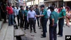 Bangladeshi police officers are seen investigating at the location where three motorcycle-riding assailants attacked secular student activist Nazimuddin Samad, in Dhaka, Bangladesh, April 7, 2016.