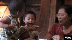 克钦族难民梅卜高在中国境内的难民营里照顾孙子。她盼望着和平到来早日回家。