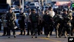 Polisi anti huru-hara mengamankan kota Ferguson, Missouri yang dilanda kerusuhan setelah penembakan seorang remaja kulit hitam.