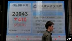 一位男士走过香港一家银行外显示香港股指的电子屏幕。(2016年1月11日)