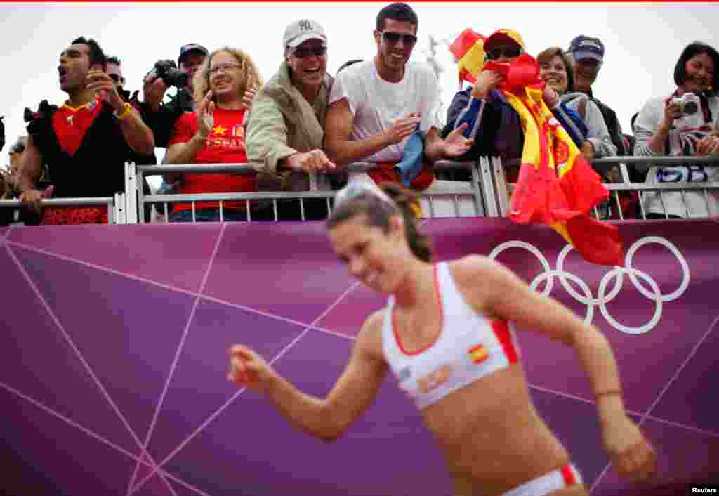 Fans cheer for Spain's Elsa Baquerizo McMillan during their women's preliminary round beach volleyball match against Argentina.