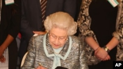 Queen Elizabeth II, Head of the Commonwealth signs the Commonwealth Charter at a reception at Marlborough House, London.