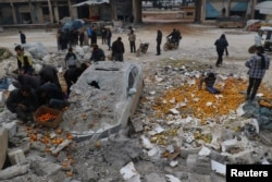 People collect scattered oranges amidst rubble after an airstrike on a market in rebel-held Maarat Mastrin in Idlib province, Syria, Jan. 14, 2017.