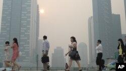 Nhân viên văn phòng đi qua lớp khói mù bao phủ Trung tâm Thương mại Singapore.