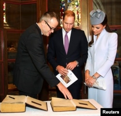 FILE - Britain's Prince William (C) and his wife Catherine, Duchess of Cambridge, (R) prepare to sign the First Fleet Bible and Prayer Book following Easter Sunday Service at St Andrews Cathedral in Sydney, April 20, 2014.