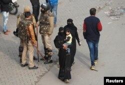 میرٹھ، اتر پردیش، پہرے پر موجود پولیس اہلکاروں کے پاس سے گزرتی باپردہ خواتین ۔ دسمبر 27, 2019 (فوٹو رائٹرز)