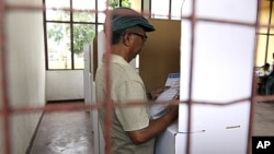 An East Timorese voter checks his ballot at a polling station during the presidential election in Dili, March 17, 2012.