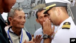 "In this photo taken Dec. 3, 2010, U.S. navy officer Michael ""Vannak Khem"" Misiewicz, right, greets his relatives at Cambodian coastal international see port of Sihanoukville, about 220 kilometers (137 miles) southwest of Phnom Penh, Cambodia. Misiewicz finally returned home Friday as commander of the U.S. Navy destroyer USS Mustin, reuniting with the relatives who wondered whether they would ever see him alive, and the aunt who helped arrange his adoption. His ship departs Monday. (AP Photo/Heng Sinith)"