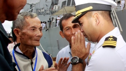 """In this photo taken Dec. 3, 2010, U.S. navy officer Michael """"Vannak Khem"""" Misiewicz, right, greets his relatives at Cambodian coastal international see port of Sihanoukville, about  220 kilometers (137 miles) southwest of Phnom Penh, Cambodia. Misiewicz finally returned home Friday as commander of the U.S. Navy destroyer USS Mustin, reuniting with the relatives who wondered whether they would ever see him alive, and the aunt who helped arrange his adoption. His ship departs Monday. (AP Photo/Heng Sinith)"""
