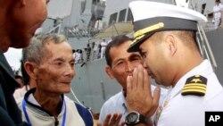 """ក្នុងរូបថតថ្ងៃទី៣ ខែធ្នូ ឆ្នាំ២០១០នេះ មន្ត្រីនាវីអាមេរិកលោក Michael """"Vannak Khem"""" Misiewicz (ស្តាំ) សំពះសាច់ញាតិនៅកំពង់ផែក្រុងព្រះសីហនុ។ លោក «ខឹម វណ្ណៈ» បានវិលត្រឡប់មកស្រុកកំណើតវិញក្នុងនាមជាមេបញ្ជាការនាវាពិឃាត USS Mustin របស់សហរដ្ឋអាមេរិក។"""