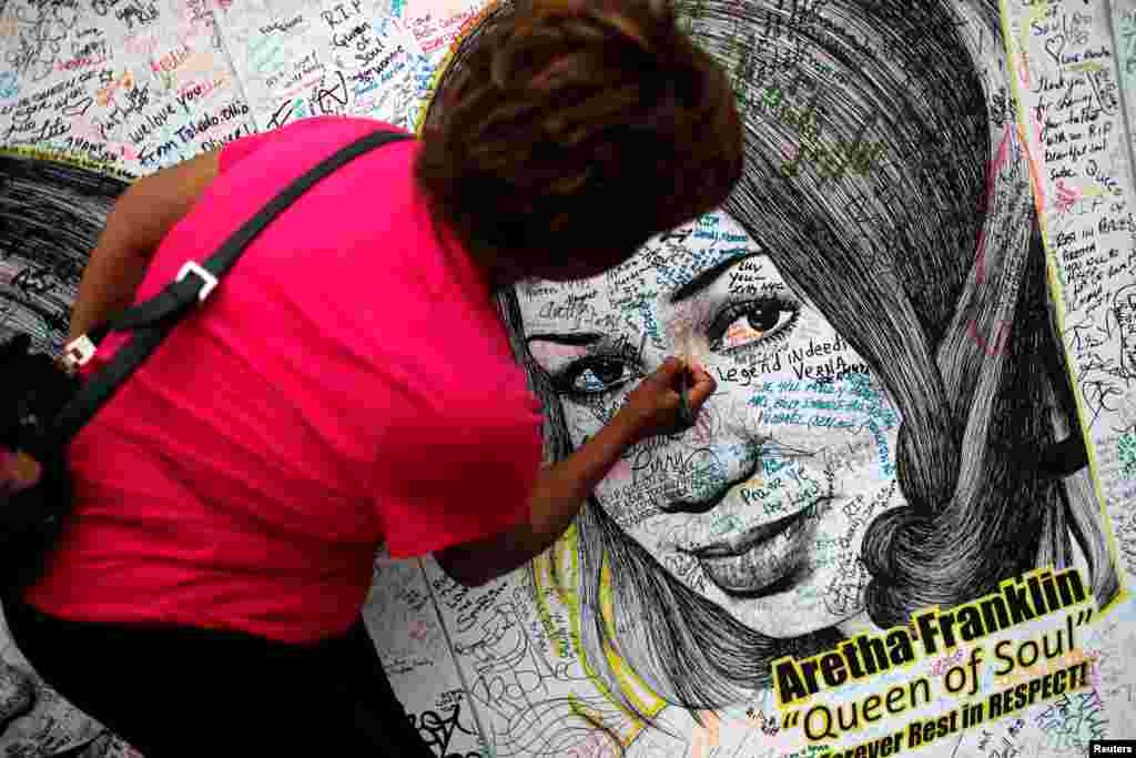 A woman writes on a large drawing of Aretha Franklin outside the Charles H. Wright Museum of African American History on the second day of a public viewing of the late singer in Detroit, Michigan, Aug. 29, 2018.