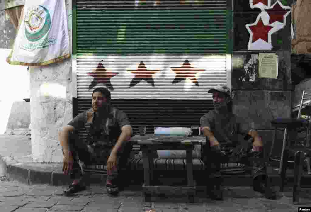 Free Syrian Army fighters sit at a checkpoint in the old city of Aleppo, August 20, 2013.