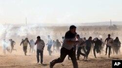 Turske bezubednosne snage koriste suzavac protiv kurdskih izbeglica na turskoj strani granice, 21. septembar, 2014.