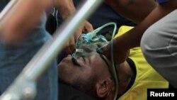 Choirul Huda, kiper Persela Lamongan, menerima perawatan medis setelah mengalami cidera dalam pertandingan melawan Semen Padang di Lamonga, 15 Oktober 2017. (Antara Foto/Rahbani Syahputra via REUTERS )