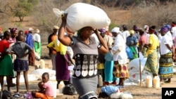 FILE: A woman carries a bag of maize distributed by the United Nations World Food Program (WFP) in Mwenezi, about 450 kilometers (280 miles) south of Harare, Zimbabwe.