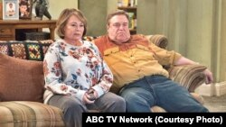 "FILE - In this image released by ABC, Roseanne Barr and John Goodman appear in a scene from the reboot of ""Roseanne."""