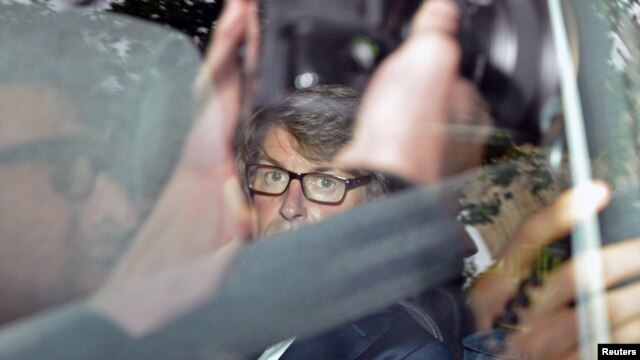 Chief Executive of G4S Nick Buckles is seen through a tinted car window as he leaves the Houses of Parliament in London, England, July 17, 2012.