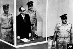 FILE - Adolf Eichmann is seen standing in his glass cage, flanked by guards, in the Jerusalem courtroom during his trial in 1961 for war crimes committed during World War II.