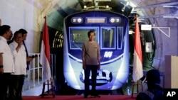 Presiden Joko Widodo berdiri di tengah panggung dengan latar kereta Moda Raya Terpadu (MRT) dalam upacara peresmian di Jakarta, Minggu, 24 Maret 2019.