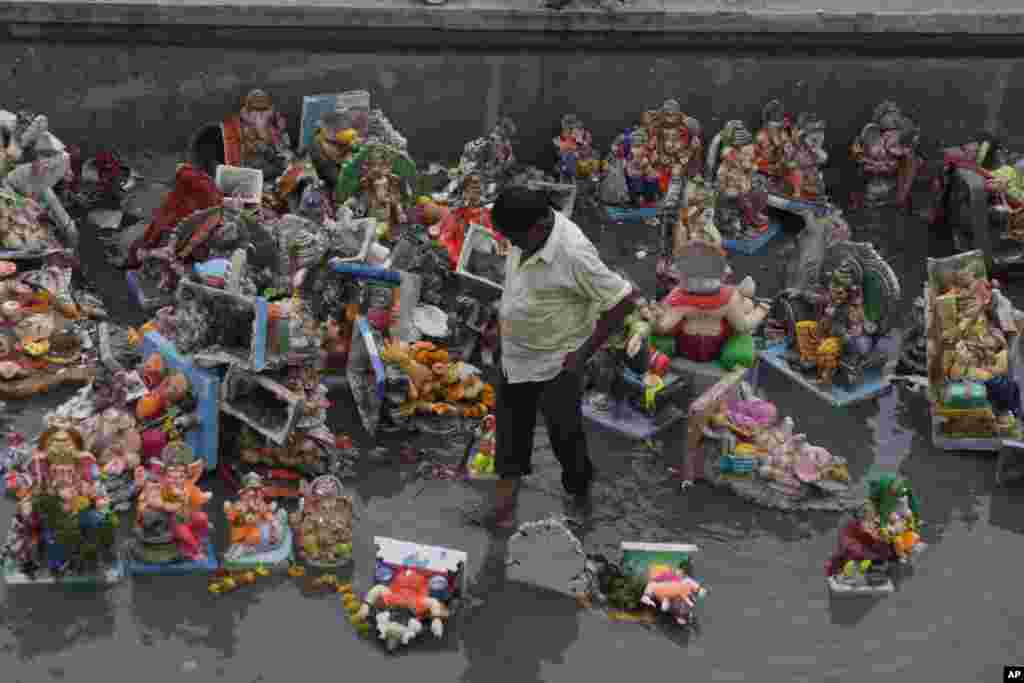 An Indian man forages for reusable items amid idols of Hindu elephant headed god Ganesha and offerings, a day after the immersion of idols, in Ahmadabad, India.