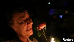 A women cries as she holds a candle and a flower outside former South African President Nelson Mandela's house in Houghton, Dec. 5, 2013.