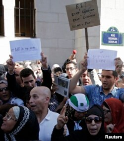 """Muslims holding signs saying """"not in my name"""" gather in front of the Paris Mosque after Friday prayers Sept. 26, 2014 to pay tribute to Herve Gourdel, a French mountain guide who was beheaded by an Algerian Islamist group, and to protest extremist tactics"""