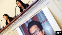 FILE - Zhang Qing, left, wife of Chinese human rights activist Guo Feixiong, and daughter Yang Tianjiao speak at a press conference before a hearing of a House Foreign Affairs Committee subcommittee in Washington, D.C., Oct. 29, 2013.