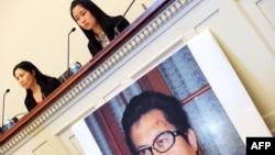 Vợ của nhà hoạt động nhân quyền Quách Phi Hùng (trái), và con gái của ông tại cuộc họp báo trước một cuộc điều trần của tiểu bang Đối Ngoại Hạ viện Hoa Kỳ trong thủ đô Washington, 29/10/13