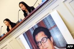 中国维权律师郭飞雄的妻子张青(左)和女儿杨天娇在参加美国国会听证会前举行记者会,讲台前有郭飞雄的照片(2013年10月29日)