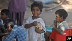 Indian street children eat food at a shanty town in Hyderabad.