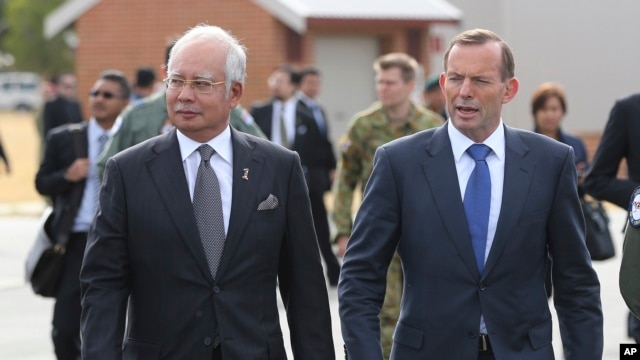 Malaysian Prime Minister Najib Razak, left, walks along the tarmac with Australian Prime Minister Tony Abbott on their way to meet crew members involved in search of wreckage and debris of the missing Malaysia Airlines MH370 in Perth, Australia, Thursday,