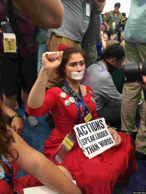یک حامی سندرز که دهان خود را با چسب بسته و مشت گره کرده است.