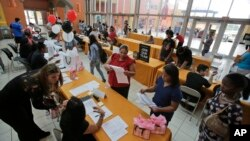 FILE - People attend a job fair at Dolphin Mall in Miami.