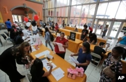FILE - People attend a job fair at Dolphin Mall in Miami. The federal government issues its October jobs report Friday, Nov. 6, 2015.