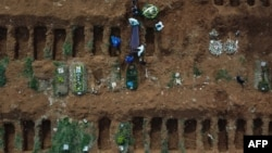Gravediggers bury an alleged COVID-19 victim at the Vila Formosa Cemetery, in the outskirts of Sao Paulo, Brazil.