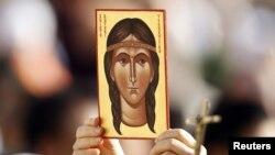 Un fiel sostiene una imagen que representa a Kateri Tekakwitha, el primer americano declarado santo por el Papa Benedicto XVI.