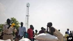 Southern Sudanese who recently returned from northern Sudan receive food rations.