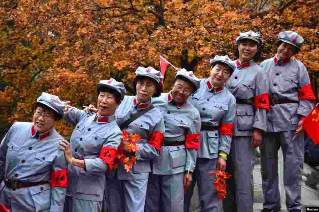 중국 베이징의 프레그런트힐스공원에서 붉은색 군복 유니폼을 입은 여성들이 단풍나무를 배경으로 사진을 찍고 있다.