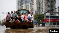 河南郑州暴雨后居民乘斗车疏散。(2021年7月23日)