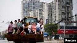 河南鄭州暴雨後居民乘坐斗車疏散。 (2021年7月23日)