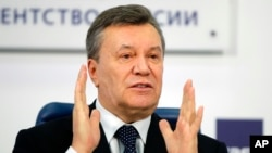 FILE - Former Ukraine President Viktor Yanukovych gestures as he speaks at a news conference in Moscow, Russia, March 2, 2018.