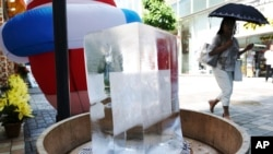 A block of ice is placed at a pedestrian street to cool down the spot in Tokyo Friday, July 20, 2018.