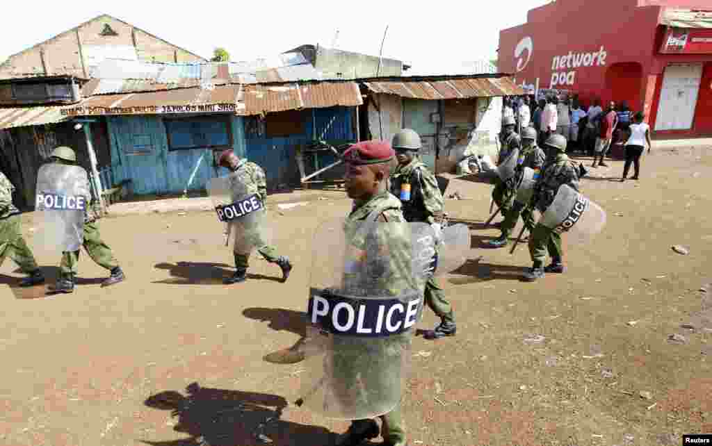 Riot police walk past residents in Nyallenda slums in Kenya's western town of Kisumu, 350km (218 miles) from the capital Nairobi as tension arises after Uhuru Kenyatta was declared winner of presidential election, Mar. 9, 2013.
